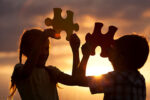 shillouette of two children holding large puzzle pieces